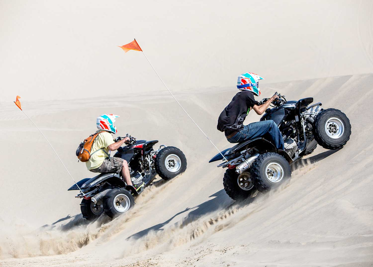 ATV renters climbing a dune on their quads